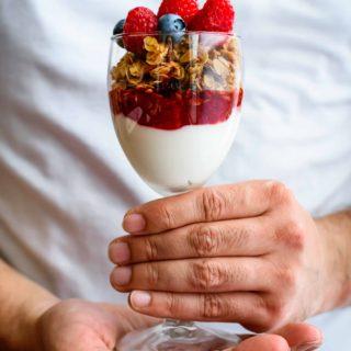 hand holding berry yogurt parfait