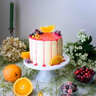 orange cake with orange buttercream frosting and cranberry drip